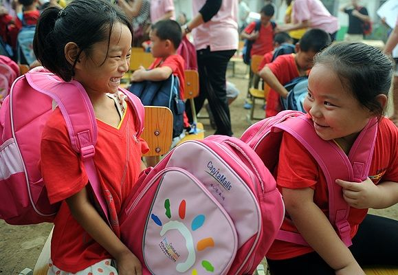 Children beneficiaries in China looking elated upon receiving their new schoolbags.